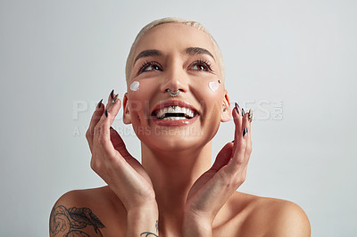 Buy stock photo Shot of a beautiful young woman applying moisturizer on her face against a grey background