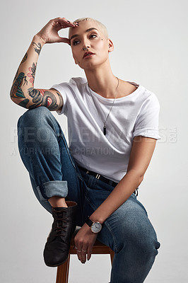 Buy stock photo Shot of a stylish young woman sitting on a stool against a grey background