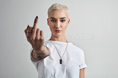Buy stock photo Portrait of an attractive young woman showing the middle finger against a grey background