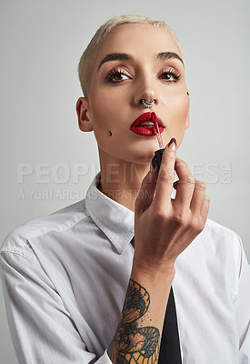Buy stock photo Portrait of an attractive young businesswoman putting on lipstick against a grey background