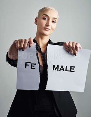 Buy stock photo Portrait of an attractive young woman holding a placard against grey background