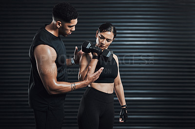 Buy stock photo Shot of a fitness trainer assisting a young woman exercising with weights against a dark background