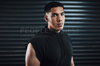 Buy stock photo Portrait of a sporty young man standing against a dark background