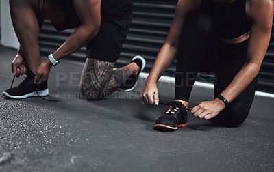 Buy stock photo Closeup shot of two sporty people tying their shoelaces while exercising together