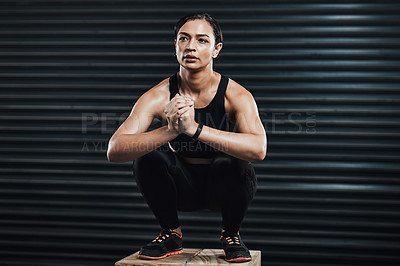 Buy stock photo Shot of a sporty young woman box jumping against a dark background