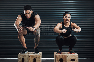 Buy stock photo Shot of two sporty young people box jumping together against a dark background