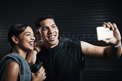 Buy stock photo Shot of two sporty young people taking selfies together against a dark background