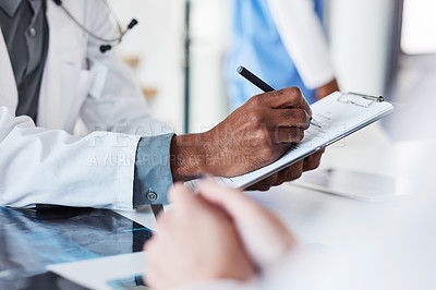 Buy stock photo Closeup shot of an unrecognisable doctor writing on a clipboard in an hospital