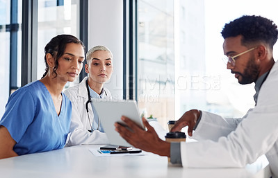 Buy stock photo Shot of a group of medical practitioners using a digital tablet together in a hospital boardroom