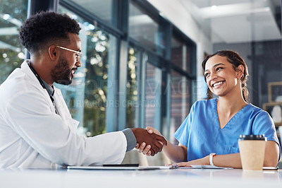Buy stock photo Shot of two medical practitioners shaking hands during a meeting in a hospital boardroom