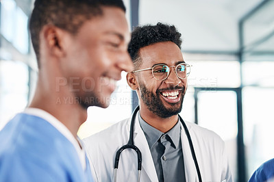 Buy stock photo Shot of a young doctor having a discussion with his colleagues in a hospital