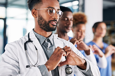 Buy stock photo Shot of a group of medical practitioners making a heart shape with their hands in a hospital