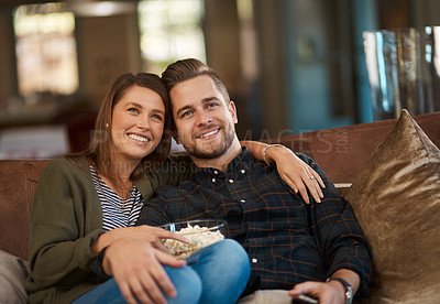 Buy stock photo Cropped shot of a young couple relaxing with popcorn on the sofa at home