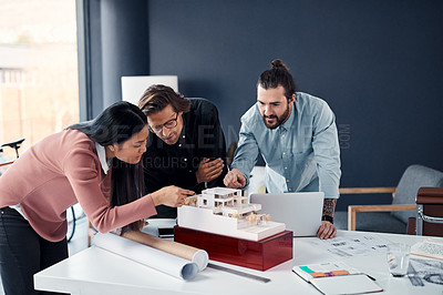 Buy stock photo Shot of three young architects working on a scale model of a modern house in their office