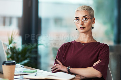 Buy stock photo Cropped portrait of an attractive young businesswoman wearing spectacles and sitting alone in her office with her arms folded