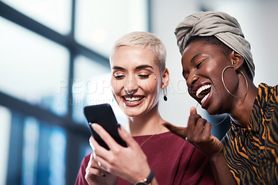 Buy stock photo Cropped shot of two attractive young business colleagues standing in the office together and laughing while using a cellphone