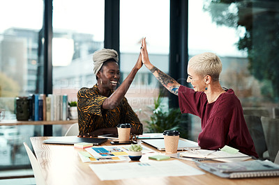 Buy stock photo Cropped shot of two attractive young businesswomen sitting in the office and giving each other a high five