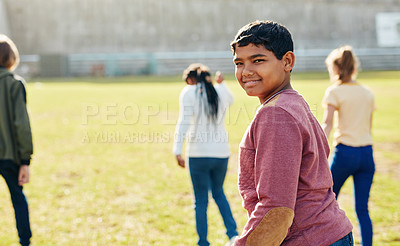 Buy stock photo Shot of a young schoolboy playing outside on a school field during recess