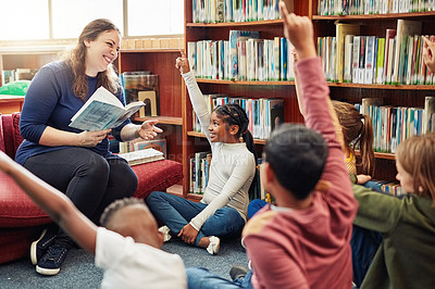 Buy stock photo Shot of a teacher reading to a group of children in a school library while they raise their hands