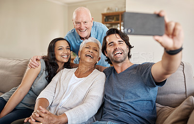 Buy stock photo Shot of a happy family taking selfies together on the sofa at home