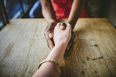 Buy stock photo Shot of two unrecognizable women holding hands together on a table