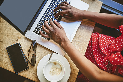 Buy stock photo Shot of an unrecognizable woman using a laptop and enjoying her coffee in a cafe