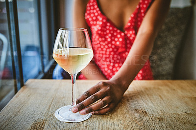 Buy stock photo Shot of an unrecognizable woman enjoying a glass of wine at cafe