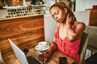 Buy stock photo Shot of an attractive young woman suffering from neck pain while working on her laptop inside a cafe