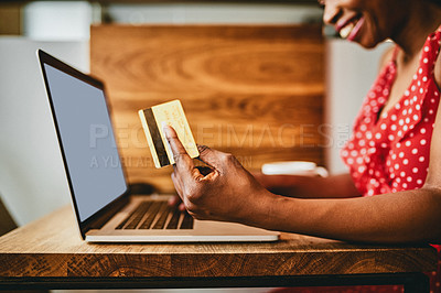 Buy stock photo Shot of an unrecognizable woman using her credit card and laptop while relaxing inside a cafe