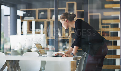 Buy stock photo Cropped shot of an attractive young businesswoman standing alone in her office and typing on her laptop