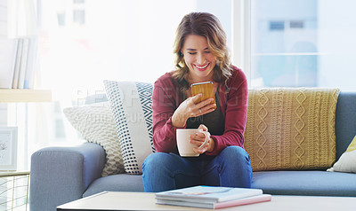 Buy stock photo Cropped shot of an attractive young woman sitting and using her cellphone while enjoying a cup of coffee at home