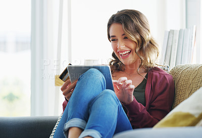Buy stock photo Cropped shot of an attractive young woman sitting on her sofa and using her tablet for online shopping