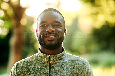 Buy stock photo Cropped shot of a sporty young man smiling at the camera while standing outdoors