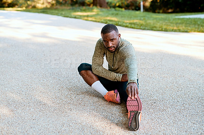 Buy stock photo Shot of a sporty young man stretching at the park before his run