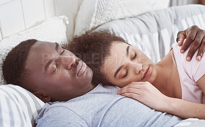 Buy stock photo Shot of a young couple cuddling while sleeping in their bed