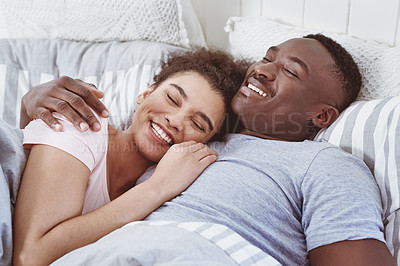 Buy stock photo Cropped shot of a happy young couple lying in bed