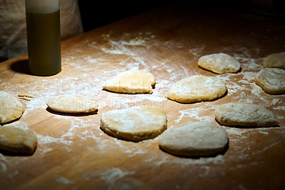 Buy stock photo Shot of raw pasta dough dusted with flour on a kitchen table