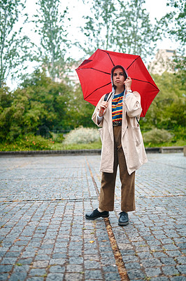 Buy stock photo Full length shot of an attractive young woman standing outside alone and holding an umbrella