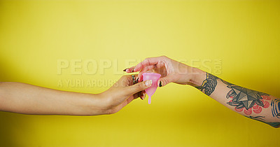 Buy stock photo Studio shot of two unrecognizable women passing a menstrual cup to the other against a yellow background