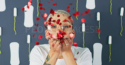 Buy stock photo Studio shot of an attractive young woman blowing red sequins against a background of sanitary pads and tampons