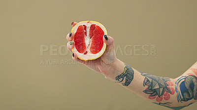 Buy stock photo Studio shot of an unrecognizable woman holding a grapefruit slice against a brown background