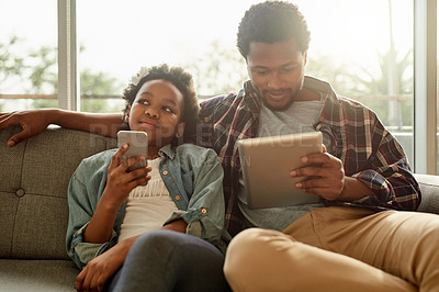 Buy stock photo Cropped shot of a cheerful young man and his daughter browsing on mobile devices together while relaxing at home
