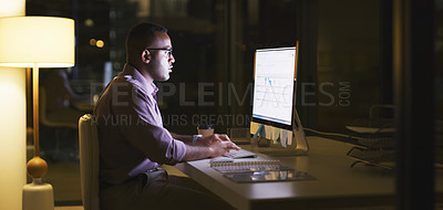 Buy stock photo Shot of a handsome young businessman working on a computer during a late shift at the office