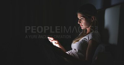 Buy stock photo Shot of an attractive young woman using her digital tablet while sitting in bed late at night