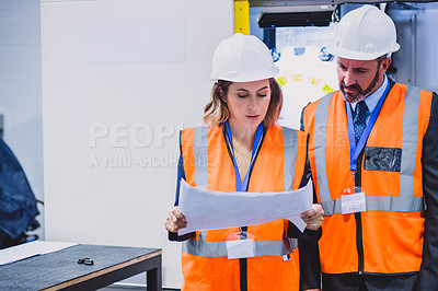 Buy stock photo Cropped shot of two focused engineers looking at blueprints together inside of a workshop