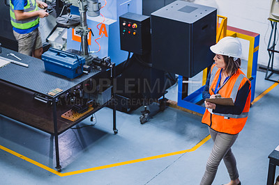 Buy stock photo Cropped shot a confident female engineer walking around and doing inspection on machinery inside of a workshop