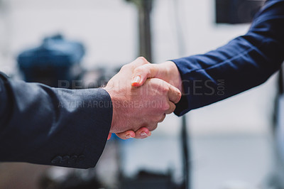 Buy stock photo Closeup of two unrecognizable businesspeople shaking hands in agreement inside of a workshop