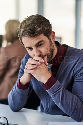 Buy stock photo Shot of a young businessman looking worried while working in an office