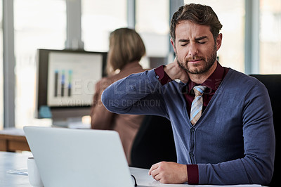 Buy stock photo Shot of a young businessman suffering with neck pain while working in an office
