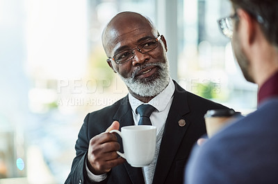 Buy stock photo Shot of two businessmen drinking coffee while having a discussion in an office